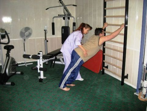 Выполняя упражнения ЛФК с помощью инструктора (как на фото), больной способствует возобновлению подвижности больных сочленений.